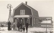 Family in front of wooden house